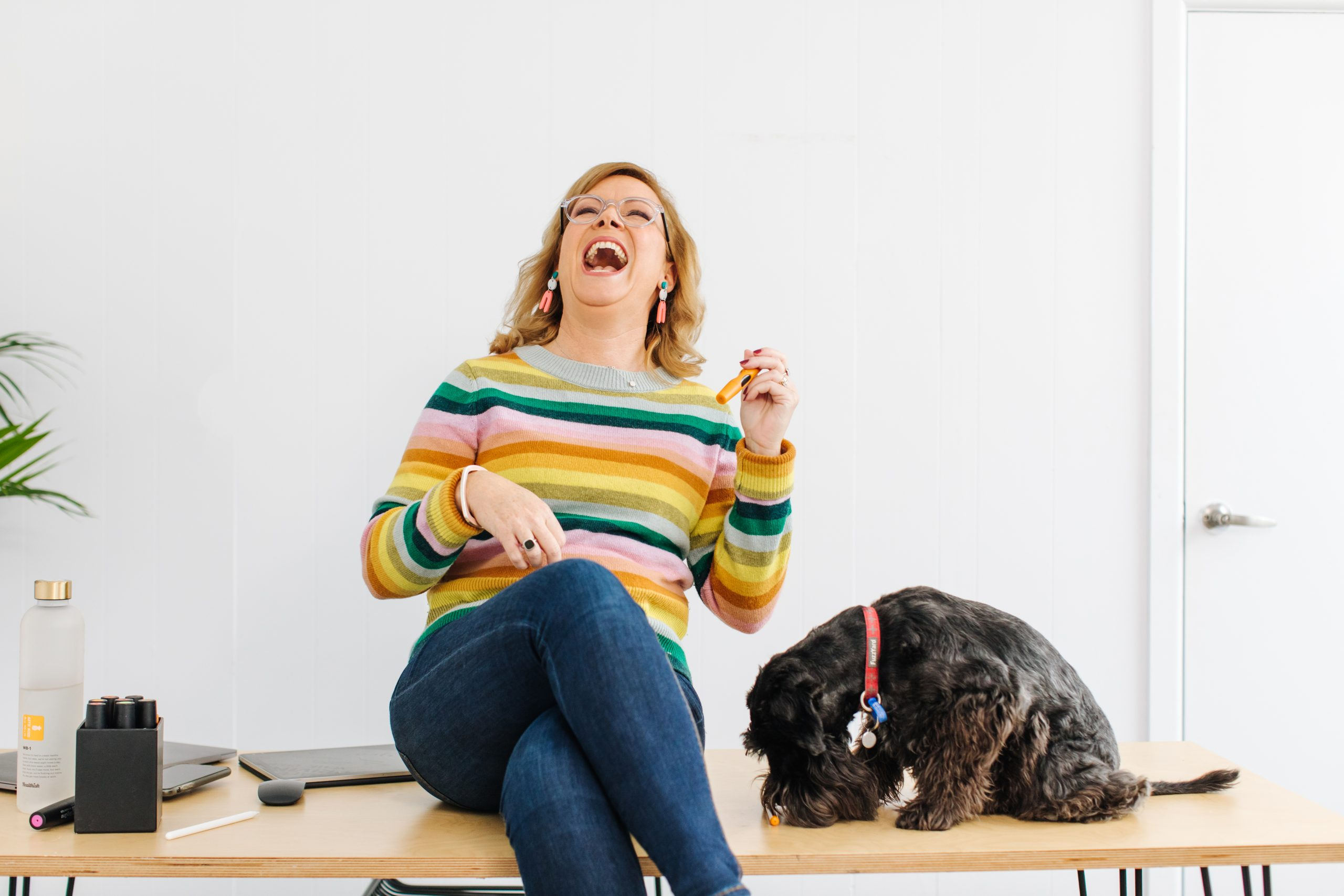 Debbie sitting on a desk with her dog having a really good laugh