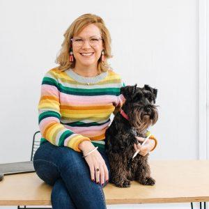 Deb sitting on a desk with her mini-Schnauzer, Otto