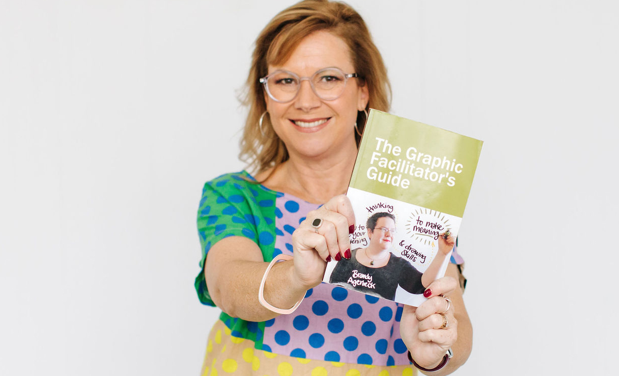 Deb holding the book Graphic Facilitator's Guide by Brandy Agerbeck